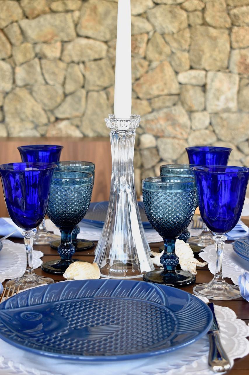 linda mesa posta azul e branca com castiçal de cristal e taças azuis