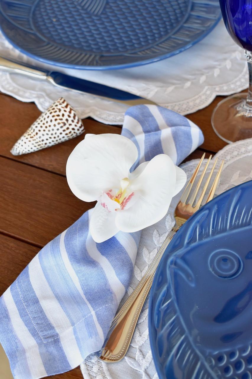 Porta guardanapo de orquídea branco combinado com guardanapo listrado azul e branco