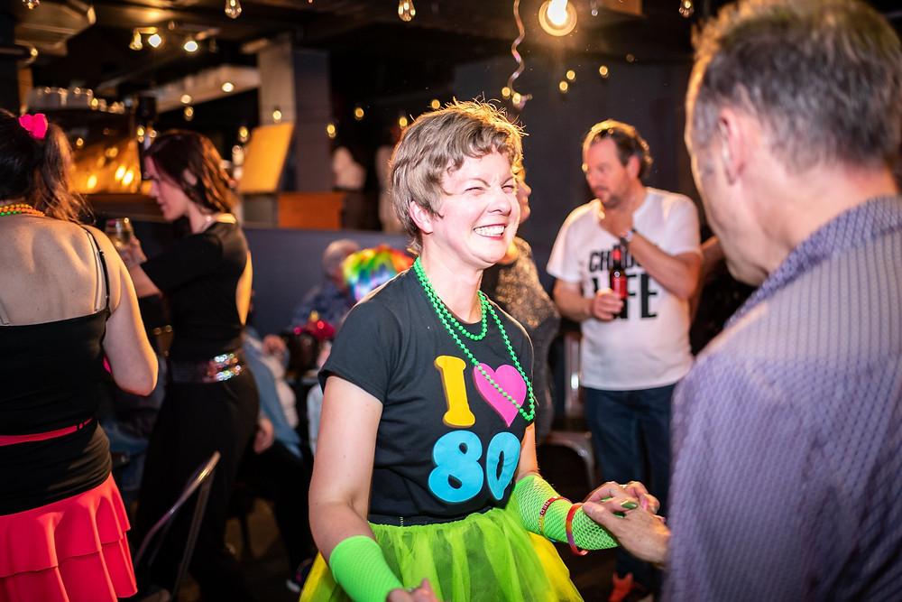 Julie dances alongside Simon Peyton at an 80s night.