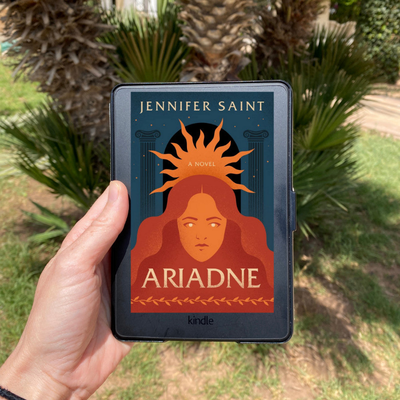 Palm Tree with book cover for Ariadne by Jennifer Saint in front of it