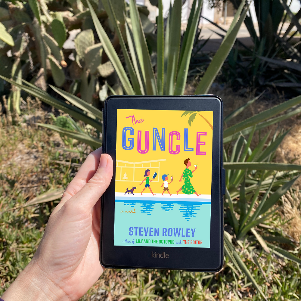 Photograph featuring the book cover of Steven Rowley's The Guncle in front of a plant