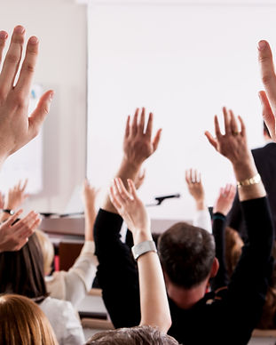 Raised hands and arms of large group of