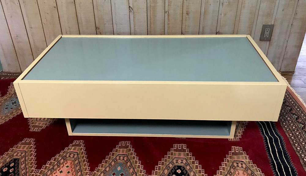 Coffee table painted in spruce blue and pear gold.