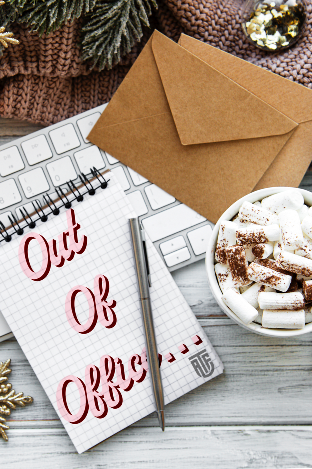 an overhead image of a very cosy, festive work desk. There is some brown envelopes, a luxurious hot chocolate topped with marshmallows and chocolate sprinkles and a note pad. On the note pad in pink cursive font reads the words 'Out of Office'