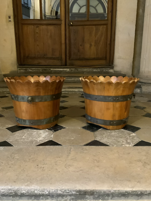 A pair of cache-pots / planters made out of wood and brass .