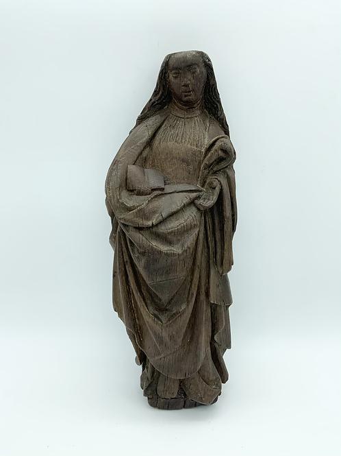 An oak sculpture of a saint .