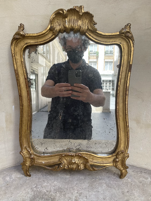 A wooden gilded mirror .