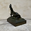 Thumbnail: A bronze statue of a lying horse on a metal base .