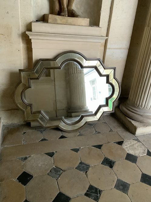 A large wooden decorative mirror with a beveled edged mirror border.