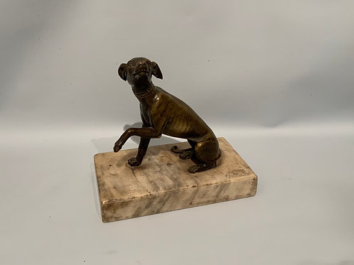 A bronze statue of a greyhound dog on a marble base .