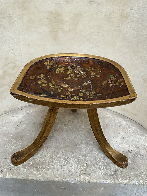 A thee legged wood gilded Egyptian style Thebes stool with copper lacquered seat