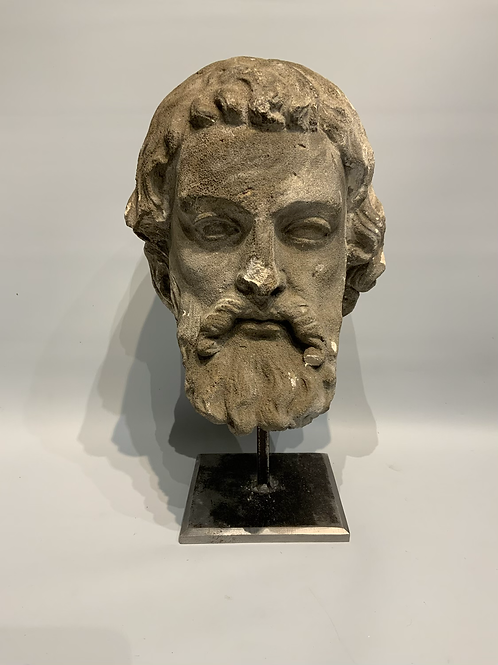 A sandstone sculpted head of a bearded man .