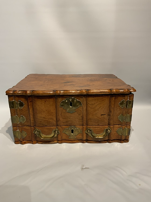 A wooden colonial box with a drawer and two compartments .