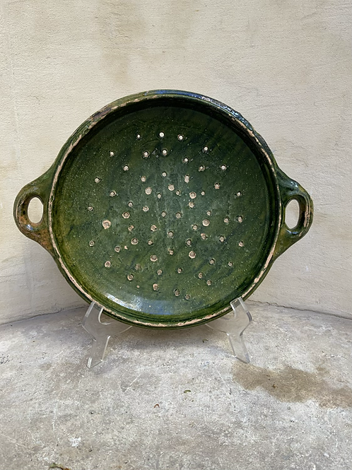 A green lead glazed strainer made in earthenware .