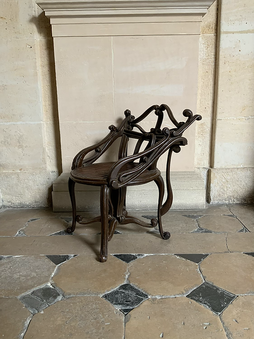 A wooden sculpted and painted chair probably for a musician .