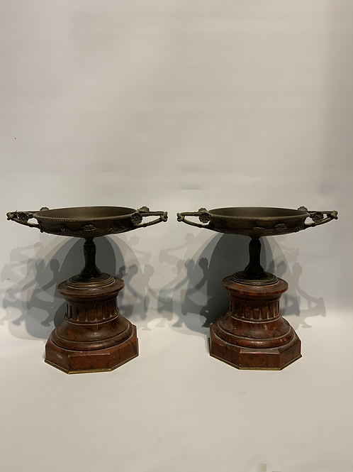 Two small bronze vases on a red marble base.