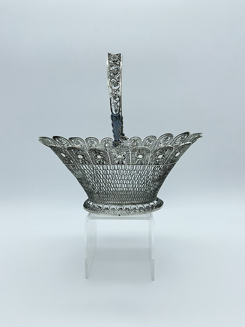 A filigree silver basket with handle .
