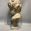 Thumbnail: A marble bust representing a child on a marble base .