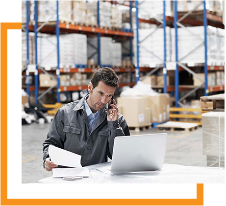 Warehose Master Planning Man in overalls on phone with laptop in warehouse