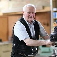 """Visbek macht Handwerk - Zimmerei Tönnies  Erlte, 8.30 Uhr, Bernard Tönnies, 84jährig, steht wie jeden Morgen in der Werkstatt und geht seiner (beruflichen/ handwerklichen) Leidenschaft nach. """"Seit 69 Jahren bin ich nun schon hier und erledige alle anfallenden Arbeiten"""", erklärt der rüstige Zimmermann und ergänzt:  Zurzeit arbeitet er an einer Holzbank, die er auf Wunsch eines Kunden anfertigt. Bernard führte den Zimmereibetrieb seines Vaters fort, der diesen wiederum von seinem Vater übernahm. So führen die Anfänge des Familienunternehmens bis in das Jahr 1860 zurück, als Johann Tönnies den Handwerksbetrieb in Erlte gründete. Nun leiten ihn Herbert Tönnies und sein Sohn Jan-Bernd, der mit seiner Meisterprüfung im Zimmererhandwerk die Fortführung zur fünften Generation sichert."""