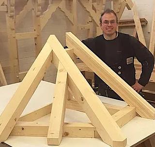 """VISBEK macht erfolgreiche Zimmerer - Zimmerei Tönnies  Stolz zeigt Simon Lindemann sein Gesellenstück: ein Waldach mit Flugsparren. Der 22-Jährige ist nun Zimmerer und kann damit seiner Leidenschaft, mit dem Werkstoff Holz zu arbeiten, vollkommen ausleben. Vor drei Jahren begann der Visbeker seine Ausbildung bei Tönnies Zimmerei & Bedachungen GmbH. """"Mein Beruf als Zimmerer macht mir viel Spaß, weil es nie langweilig wird"""", verrät Simon und ergänzt: """"Hier gibt es immer wieder neue Herausforderungen, weil jede Baustelle anders ist und der Einsatz von unterschiedlichen Baustoffen und Materialien sehr abwechslungsreich sind."""""""