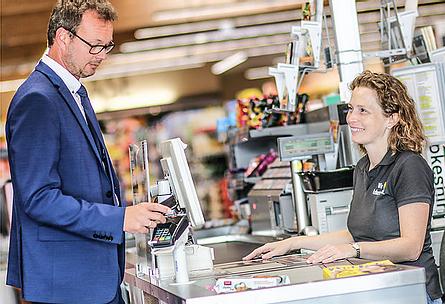 """VISBEK macht bezahlen in Sekundenschnelle - Volksbank  Visbek💸📲 Kontaktlos in Sekundenschnelle bezahlen Neue Funktionen Ihrer Volksbank-BankingCard / auch mit Ihrem Smartphone   Im Vorbeilaufen an Kassen im Supermarkt und Geschäften bezahlen, ist dank der neuen digitalen Karten der Volksbanken möglich. """"In Sekundenschnelle kann man so ganz einfach bezahlen"""", erklärt Olaf Arlinghaus, Experte für Zahlungsverkehr und Karten bei der Volksbank Visbek eG.  KARTE EINFACH AUFLEGEN Die Bezahlung erfolgt """"kontaktlos"""" mit der eigenen VR-BankingCard. """"Diese muss beim Bezahlvorgang lediglich auf das Terminal im Geschäft gelegt werden"""", so Arlinghaus. Bei Beträgen unter 25 Euro funktioniert dies ohne Unterschrift oder PIN, was das Bezahlen besonders für kleine Beträge enorm beschleunigt. Ist der Rechnungsbetrag höher als 25 Euro, muss aus Sicherheitsgründen nach dem Auflegen der Karte die PIN eingegeben werden. """"Ob Ihre Bankkarte diese neue Funktion unterstützt, zeigt das Symbol darauf"""", weiß auch Michael Nielsen, Inhaber des EDEKA-Marktes in Visbek: """"Das Symbol ähnelt einem WLAN-Zeichen.""""  IM HERBST ERHALTEN ALLE KUNDEN NEUE KARTEN Die Volksbank Visbek eG händigt ihren Kunden seit einigen Monaten ausschließlich diese modern ausgestatteten EC-Karten aus. """"Einige Kartenbesitzer profitieren jedoch noch nicht von dieser neuen Funktion, sodass im Herbst alle unsere Kunden neue Bankkarten per Post erhalten"""", verrät Kundenbetreuer Jens Backhaus. Alle neuen Karten verfügen über die """"Kontaktlos-Funktion"""".  KONTAKTLOS BEZAHLEN AUCH MIT DEM SMARTPHONE Anstelle Ihrer Bankkarte, können Sie auch Ihr Smartphone nutzen, um kontaktlos zu bezahlen. Dafür halten Sie lediglich ihr Handy über das Terminal. Schnell und einfach können sie diese Funktion in Ihrer VR-BankingApp freischalten. Wenn Sie Fragen dazu haben, wenden Sie sich gerne an unsere Mitarbeiter.  BARGELD AN DER (SUPERMARKT-) KASSE ABHEBEN Darüber hinaus ist es in immer mehr Geschäften möglich, direkt an der Kasse (beim Bezahlen) Bargel"""