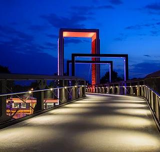 """VISBEK macht leuchtende Brücken - Schulz Systemtechnik  Eine Brücke der ganz besonderen Art für Fußgänger, Rollstuhlfahrer und Radfahrer verbindet jetzt den Zitadellenpark in Vechta und die westlichen Baugebiete mit der City. Zusammen mit dem neuen Mobilitätszentrum, Stadthäusern und einer Parkgarage wird sie zum Aushängeschild der Kreisstadt. """"Die Brücke ist sowohl architektonisch als auch technisch ein Meisterwerk"""", sagt Carsten Kremer, Projektleiter bei SCHULZ Systemtechnik. """"Sie steckt voller Intelligenz, was die Lichtsteuerung angeht.""""  Sobald jemand über die Brücke schreitet, wandert das Licht sozusagen mit ihm und wird langsam hinter ihm wieder heruntergedimmt, bis es schließlich ganz erlischt. Dazu erfassen Bewegungssensoren die genaue Position der Brückennutzer. Verschiedene Lichtszenarien gibt es außerdem beim Aufzug und bei den Pylonen. Absolutes Highlight ist der große Pylon in der Mitte des imposanten Bauwerks. """"Durch die eindrucksvolle Illumination fällt er schon von weitem ins Auge"""", sagt der Lichtexperte. """"Seine indirekte Anstrahlung in unterschiedlichen Farben sorgt für ein außergewöhnliches Ambiente und bietet zahlreiche Effekte."""" Hierzu verbaute SCHULZ Systemtechnik eine Menge Lichtleisten, die jeweils mit 32 LED bestückt sind und durch die RGBW-Technik in nahezu unendlich vielen Farbnuancen erstrahlen können.    SCHULZ Systemtechnik realisierte die komplette Elektrotechnik. """"Allein für das Verlegesystem haben wir Kabelrinnen mit über 13 Kilometern Leitungen installiert"""", so Kremer. """"Alles unsichtbar"""", betont er. So verschmelzen Elektrotechnik und Brückenkonstruktion zu einer Einheit. Auch ein Videoüberwachungssystem werden die Visbeker noch anbringen.    """"Die Intelligenz, die im Beleuchtungssystem steckt, ist in dieser Form einmalig"""", fasst der Projektleiter zusammen. Vechta profitiert nicht nur von energetisch optimalen Bedingungen und modernster LED-Technik, um die Stromrechnung gering zu halten."""