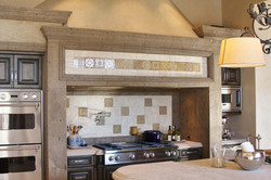 1-Range-Hood-Surround-in-Tobacco-Cantera-Stone-with-Distressed-Finish-with-Deco-Tile-Inserts
