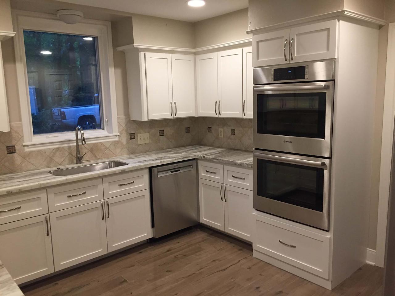 white decor kitchen with steel appliance installations