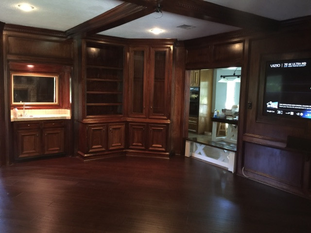 fully custom entertainment room with custom wood cabinetry and wood floors