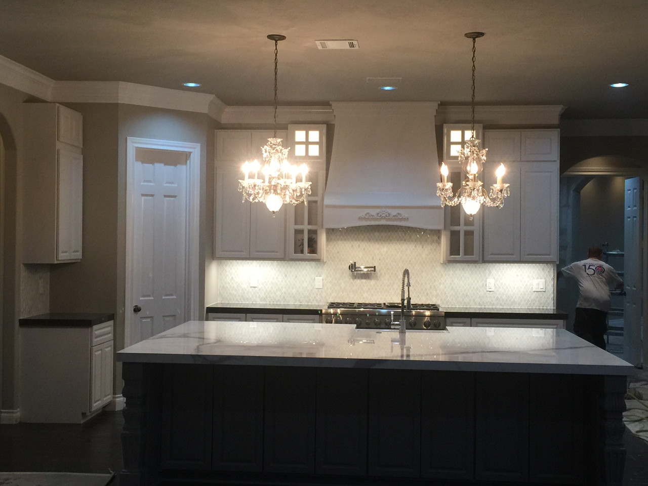 custom floating marble bar in the kitchen with overhanging chandeliers