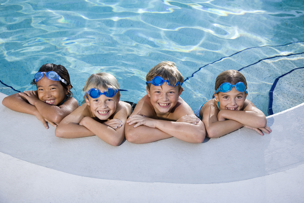 4 kids sitting smiling at edge of pool