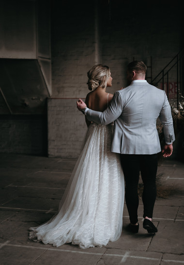 Groom with arm around bride