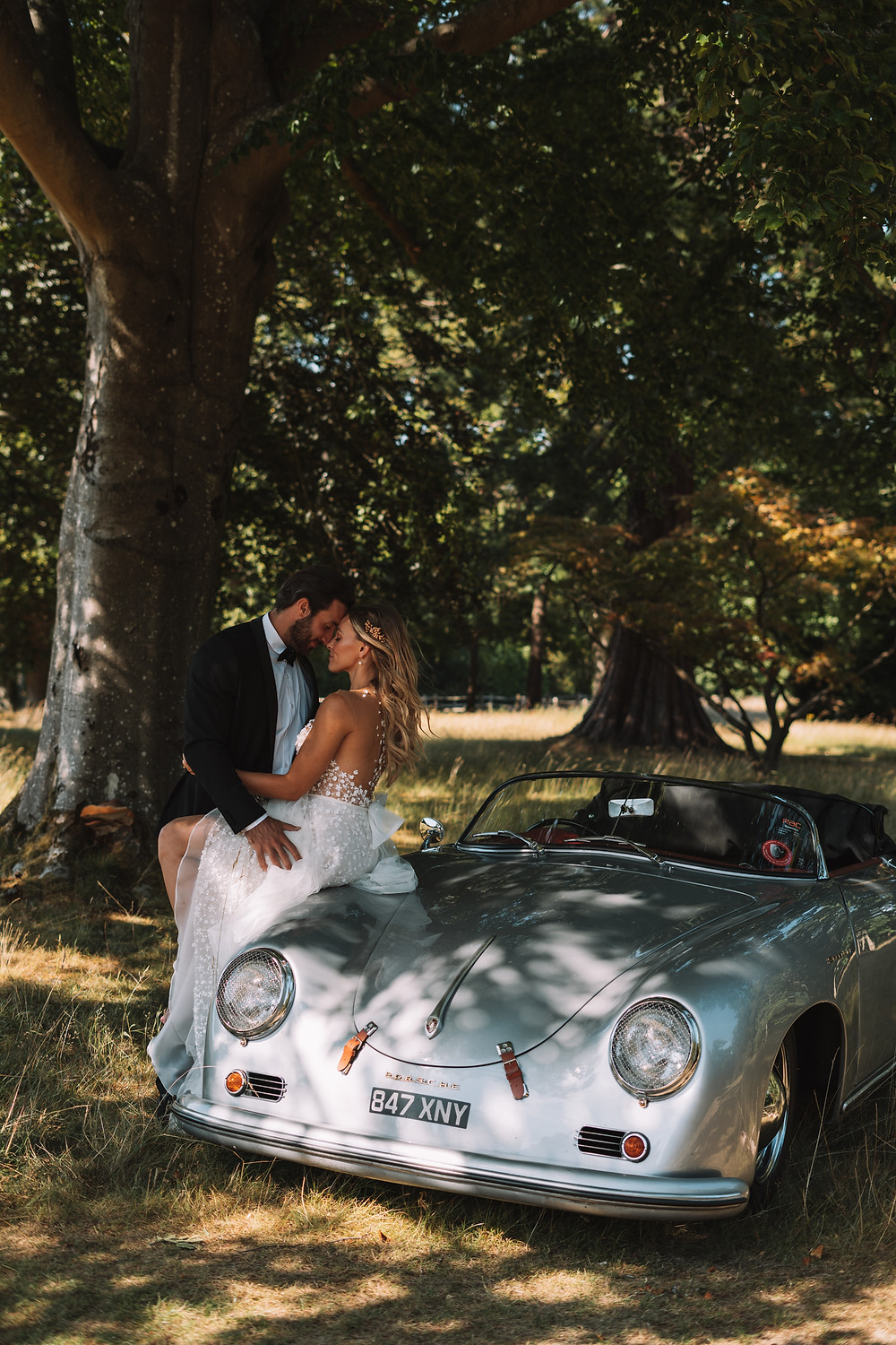 Bride sat on classic car with legs wrapped around groom