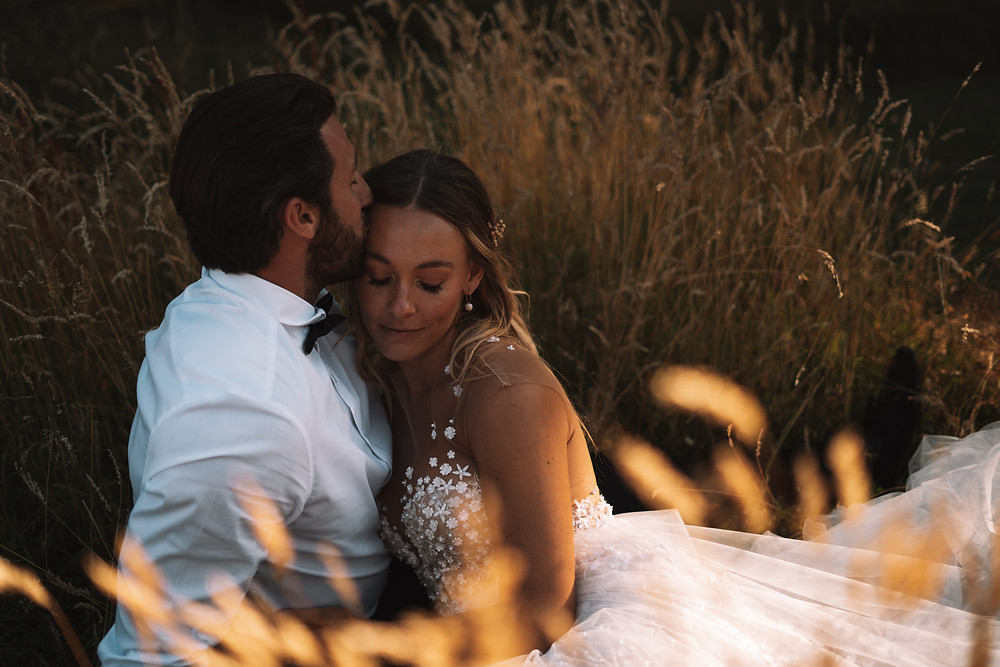 Groom kisses brides temple as they sit together in golden grass
