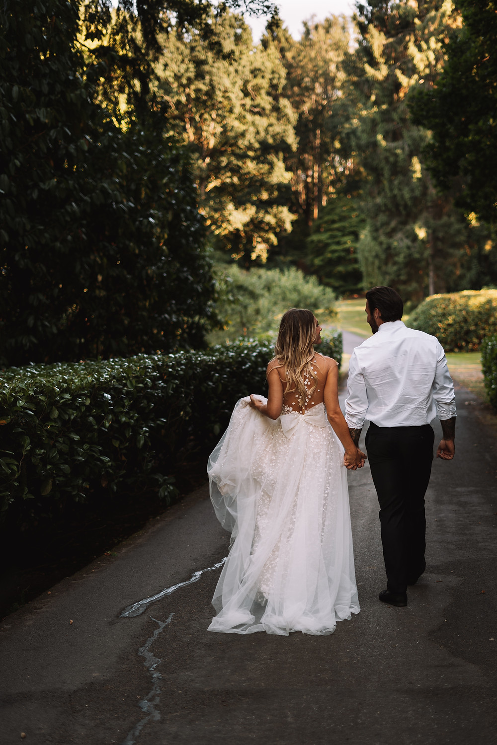 Bride & groom holding hands as they walk towards trees