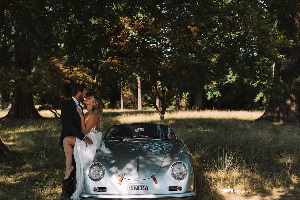 Bride sat on class car with head tilted towards groom