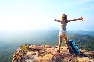 Young happy woman with backpack standing on a rock with raised hands and looking to a vall