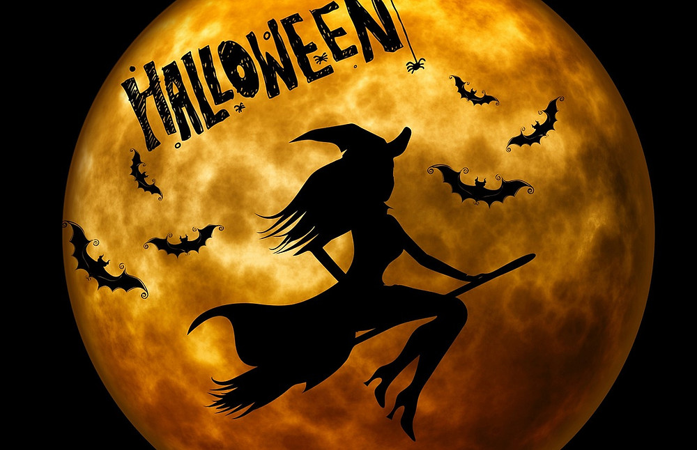 Witch on broomstick and bats flying across golden Halloween moon
