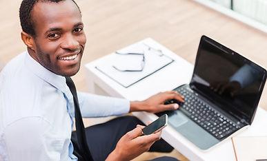 Homem de sorriso no portátil