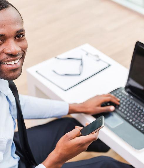 Sourire homme sur ordinateur portable