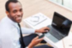 Hombre sonriente en la computadora portá
