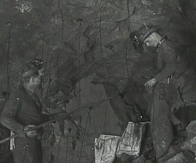 Miners loading round with powder sacks on ground circa 1940's