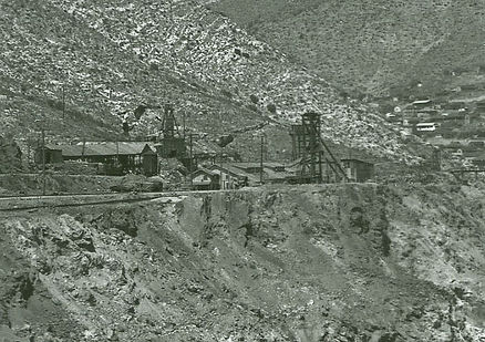 Photo of four mine headframes, on the left is the Charon, then the Reese shaft still with a tiny hoist house, with the Holbrook #2 mine immediately behind the Reese. A fourth headframe of an unknown shaft can faintly be seen on the ri