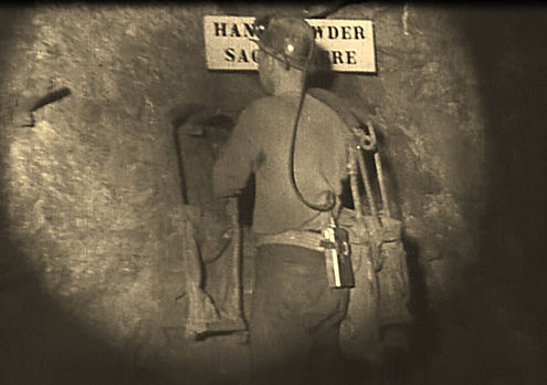 Miner hanging up empty powder sacks Junction mine circa 1940's