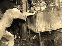 miner hand tramming mine car
