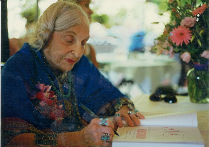 Beatrice Wood signing the cookbook she illustrated.
