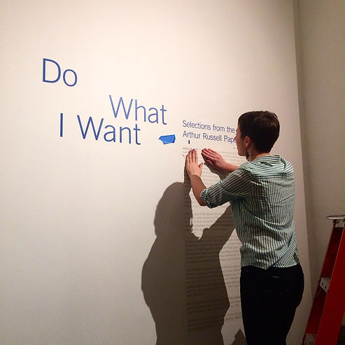 Mary Rhymer appies custom vinyl lettering for an exhibition at the Brooklyn Academy of Music