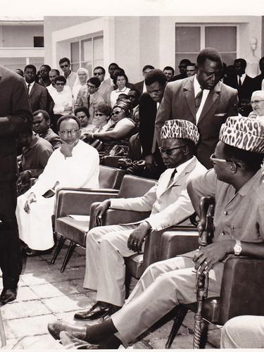 Monsieur Paul Mushiete, ministre de la Culture, prononçant le discours inaugural. Assis, à droite, en toque de léopard, les Présidents L. S. Senghor et J. D. Mobutu, Kinshasa.