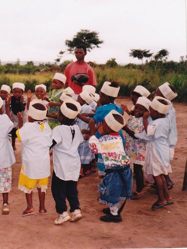 Bénédiction du lieu par le curé, J. C. Mutoka. Les enfants exécutent une chanson et jouent avec leurs institutrices. 24 décembre 1999.